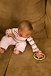 baby girl 7 months old sitting leaning over to pick up toy