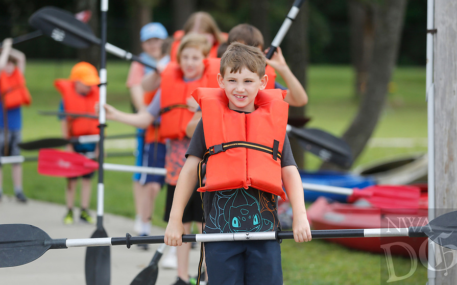 Oliver Noack, 8, stands in line Tuesday, June 8, 2021, with paddle and lifejacket to kayak with his group during the city of Fayetteville Parks and Recreation Outdoor Adventure Be Active summer camp at Lake Fayetteville. The week long morning camp offers activities that include disc golf, climbing, mountain biking, kayaking and others. Check out nwaonline.com/210609Daily/ and nwadg.com/photos for a photo gallery.<br /> (NWA Democrat-Gazette/David Gottschalk)