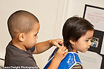 Education preschool art activity painting at easel boy helping friend put on smock 3 year olds horizontal