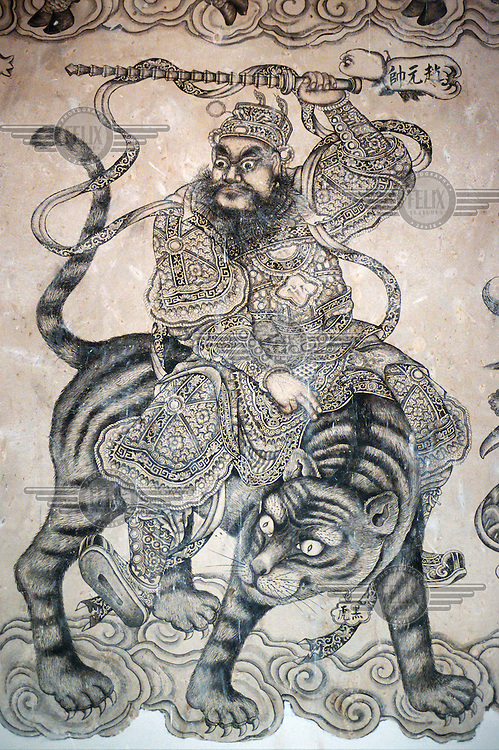 Chinese painting of a warrior sitting on a tiger, on a wall of the Khoo Kongsi clanhouse, the most elaborate of all clanhouses on Penang Island. Designed to capture the splendour of an imperial palace, it has a seven-tiered pavilion, dragon pillars and hand-painted walls. The original design was so ambitious that conservative Khoo clansmen cautioned against it, lest the emperor of China be offended. The building was completed in 1902, but on the first night it was finished, the roof mysteriously caught fire. The Khoos rebuilt it on a more modest scale.