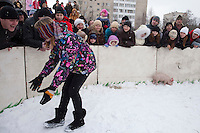 Istra, Russia, 06/03/2011..A blindfolded teenage girl chases a piglet as people celebrate Maslenitsa, also known as Butter Week or Pancake Week. Maslenitsa marks the beginning of the Russian Orthodox period of Lent, but is a traditional Russian Holiday marking the end of winter, and has its origins in pagan times.