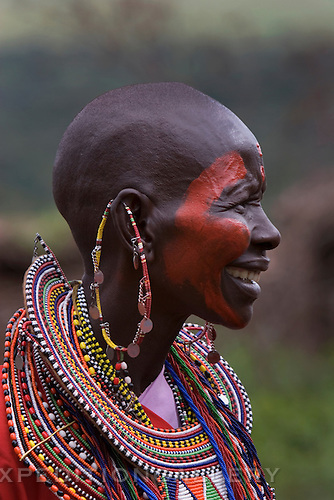 A native Maasai woman with face paint, shaved head, and traditional decorative earrings and beaded necklaces, Kenya. [NO MODEL RELEASE]