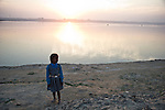 Child playing by the Ganges River in Allahabad for Kumbh Mela Festival.