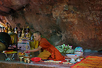 Buddhist Monk preparing for a small ceremony at a cave temple in the Phnom Kulen area, Cambodia
