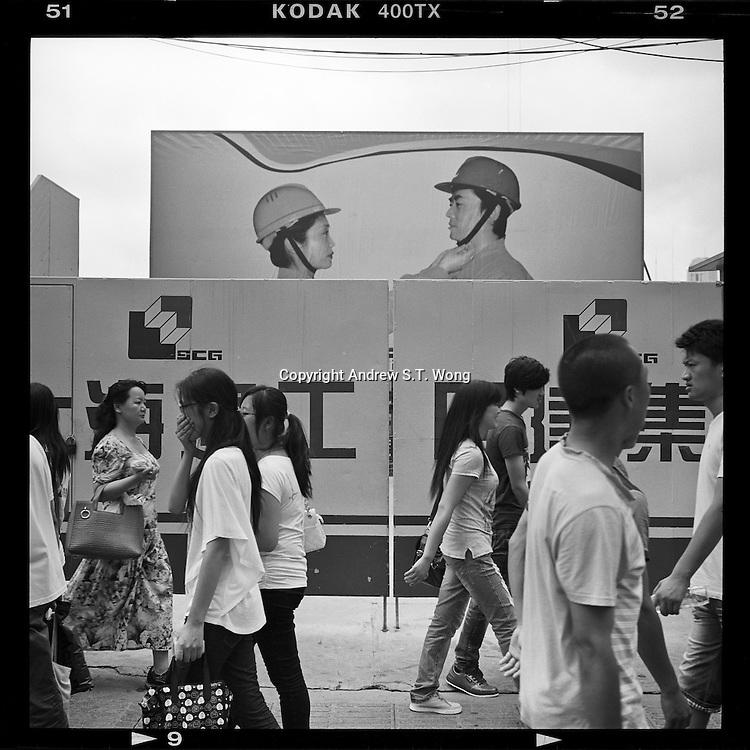 Pedestrians walk past a construction site in Shanghai, China, August 2012. (Mamiya 6, 75mm, Kodak TRI-X film)