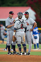Danville Braves pitching coach Willie Martinez (right) has a meeting on the mound with starting pitcher Matt Withrow (12) and catcher Carlos Martinez (8) during the game against the Burlington Royals at Burlington Athletic Park on July 12, 2015 in Burlington, North Carolina.  The Royals defeated the Braves 9-3. (Brian Westerholt/Four Seam Images)