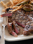 Close up of a grilled t-bone steak on a plate with a fork, thin-cut french fries and grilled artichoke hearts.