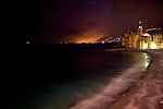 The beach of Camogli within the night with dramatic, quite surreal light. View to the church / Basilika di Santa Maria Assunta and the castle / Castel Dragone. Blue and orange colors contrasting. City of Genova far at the horizon seems to be burning because of the reflections at the clouds.