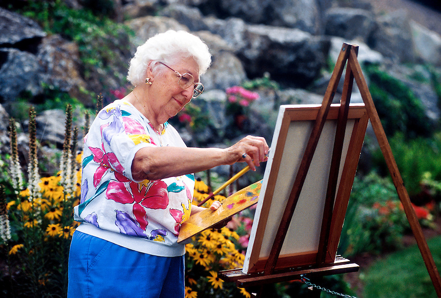 Portriat of a senior woman painting in her garden.