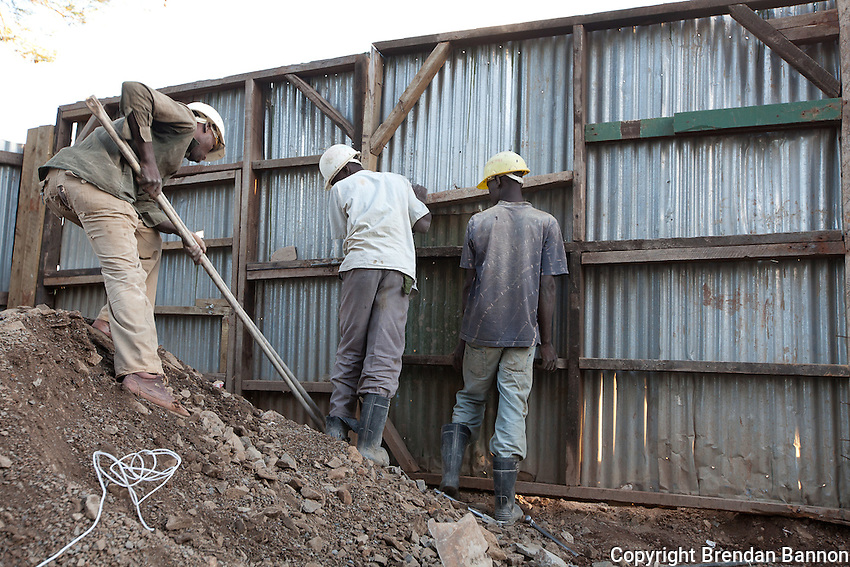 Workers installing a barrier between the construction site and  the street on Ngong road in Nairobi, Kenya.