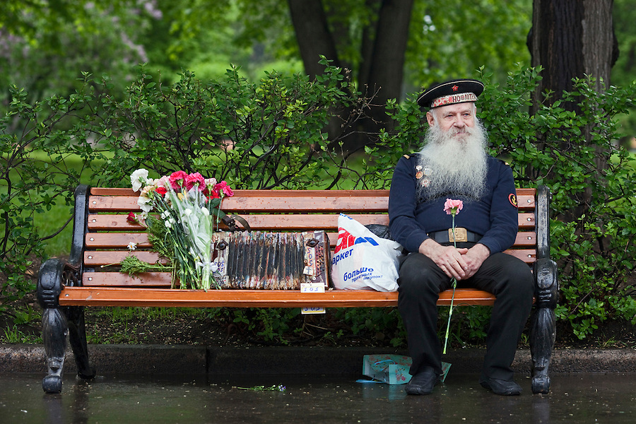 Moscow, Russia, 09/05/2012..A naval veteran sits with an accordian and flowers he has been presented as Russian World War Two veterans and well-wishers gather in Gorky Park during the countrys annual Victory Day celebrations.