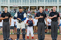 Umpires Andrew Barrett, Brian Walsh, and Darius Ghani flank catcher Tony Sanchez and a young fan during the national anthem before a Texas League game between the Amarillo Sod Poodles and Frisco RoughRiders on May 16, 2019 at Dr Pepper Ballpark in Frisco, Texas.  (Mike Augustin/Four Seam Images)