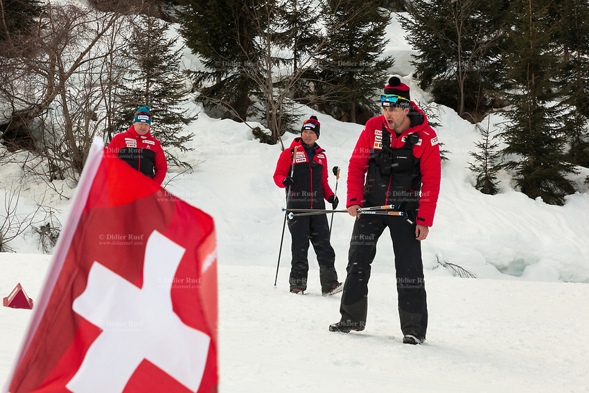 Switzerland. Canton Ticino. Swiss-Cups Campra. Cross Country Skiing. FIS Classic Sprint Race. Bernhard Aregger (L) is the CEO of Swiss-Ski. Hippolyt Kempf (C) is the Cross Country Skiing Chef by Swiss-Ski and holds two ski poles. A Swiss-Ski trainer (R) encourages the skiers during the race. Hippolyt Kempf (born 10 December 1965) is a Swiss Nordic combined skier who competed during the late 1980s and early 1990s. He won a complete set of Olympic medals, earning two of them at the 1988 Winter Olympics in Calgary (gold: 15 km individual, silver: 3 x 10 km team) and the third at the 1994 Winter Olympics in Lillehammer (bronze: 3 x 10 km team). Kempf also earned a 3 x 10 km team silver medal at the 1989 FIS Nordic World Ski Championships in Lahti. The italian competito. A swiss flag used by Swiss-Ski as symbol of its belonging to Switzerland. Swiss-Ski is a branch of Swiss Olympic. The Fédération Internationale de Ski (FIS; English: International Ski Federation) is the world's highest governing body for international winter sports. Founded  on 2 February 1924, it is responsible for the Olympic disciplines of cross-country skiing. The FIS is also responsible for setting the international competition rules. 4.01.2020 © 2020 Didier Ruef