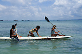 Itaparica Island, Brazil. Tourist children paddling a surfboard in the sunshine with boats behind. Bahia State.