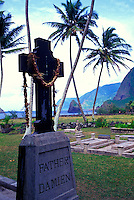 Father Damien's headstone draped with a lei, with Okala Island (aka Musubi Rock) in the background. The grave is located outside of St. Philomena Church in the Kalawao district on the Kalaupapa peninsula