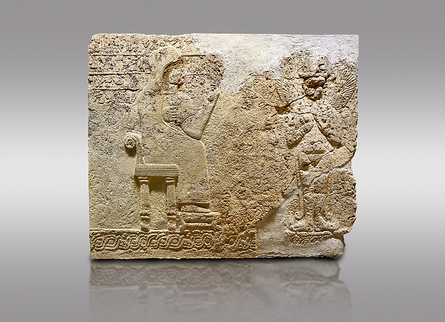 """Picture & image of Hittite relief sculpted orthostat stone panel  of Long Wall Limestone, Karkamıs, (Kargamıs), Carchemish (Karkemish), 900-700 BC. Anatolian Civilisations Museum.<br /> <br />  The hieroglyphics reads; """"I am Win-a-tis, beloved wife of my Lord Suhi, wherever and whenever my husband honours his name, he will honour my name as well with favours"""". Underneath, there are two goddess figures, one is naked with a horned head, holding her breasts with her hands. Her genitalia is indicated by a triangle. <br /> <br /> On a gray background."""
