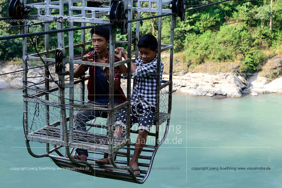 NEPAL , Mugling, village Karantar, children in cable car on river Daraudi / Kinder in einer Seilbahn am Fluss Daraudi