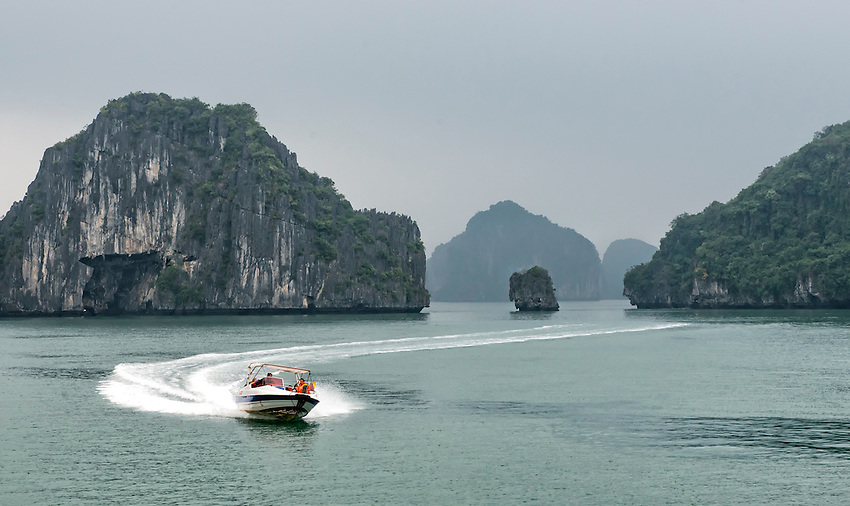 """A speedboat zooms across a section of Ha Long Bay. Ha Long Bay, located on the east coast of Vietnam near Haiphong, contains over 1,900 limestone """"karst"""" islands projecting from the sea."""