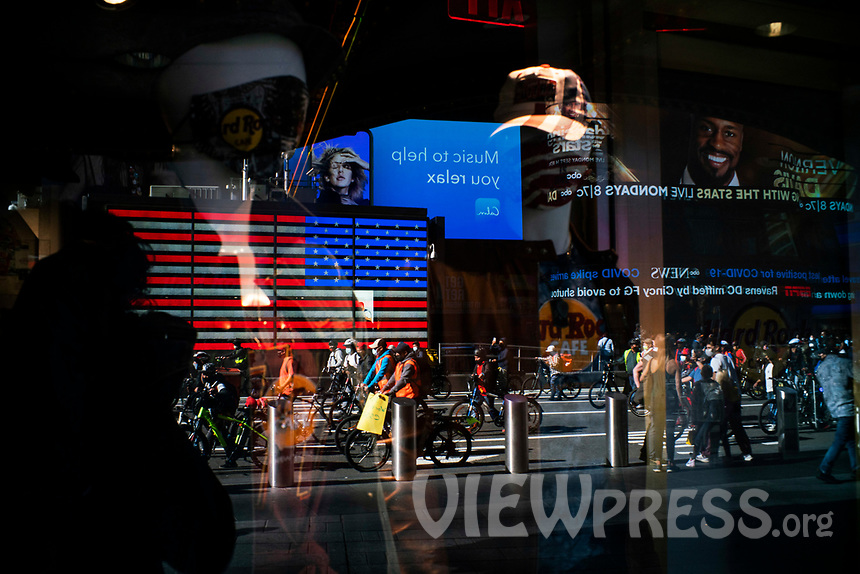 NEW YORK, NY - OCTOBER 15: Delivery workers as reflected on a window as they take part in a protest to stop thefts of their bikes at Times Square on October 15, 2020 in New York, At least 4,477 bicycles have been reported stolen with an increase of 27 percent from same period last year, according to the police. (Photo by Eduardo MunozAlvarez/VIEWpress)