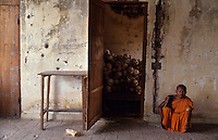 A Buddhist monk outside a temple which was turned into a killing field by the Khmer Rouge during their reign of terror between 1975 and 1979. The bones of some of the victims are still piled there.