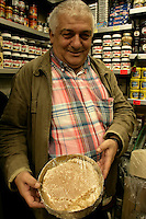 Turkish shopkeeper shows honey on the comb in his shop in Eminonu, Istanbul, Turkey
