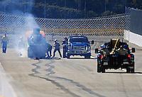 Feb. 27, 2011; Pomona, CA, USA; NHRA safety safari crews extinguish fire from the car of funny car driver Bob Bode after having an engine fire during the Winternationals at Auto Club Raceway at Pomona. Mandatory Credit: Mark J. Rebilas-