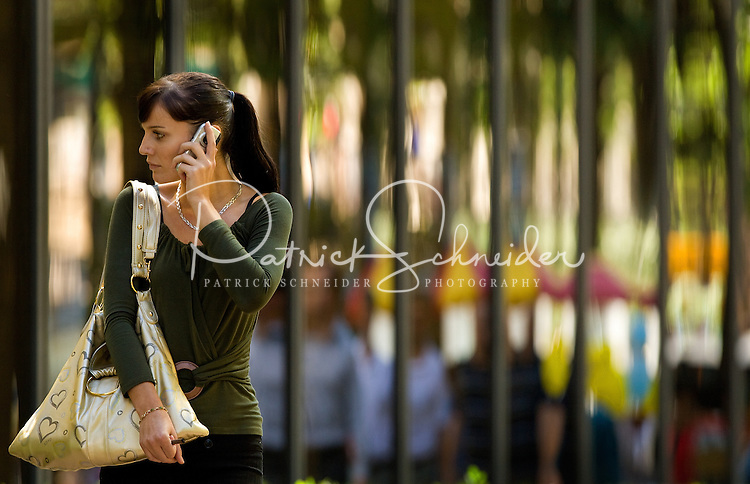 A young business professional talks on a cell phone in uptown Charlotte, NC.
