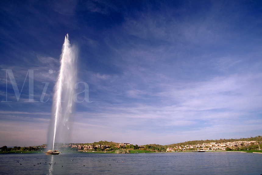 The Fountain is a 560-ft. tall jet of water which shoots up from a 28-acre lake in the center of Fountain Hills, AZ. The display continues for 15 minutes every hour on the hour daily from 10 -00 AM to 9 -00 PM. Fountain Hills Arizona USA Phoenix.