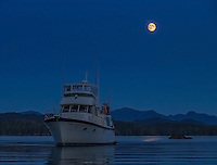 The motor yacht Great Bear II sits at anchor as the moon rises over coastal British Columbia.
