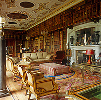In the library over 17,000 leatherbound volumes line the walls. The 17th century ceiling features roundels by Verrio and the sofas and chairs came from Devonshire House