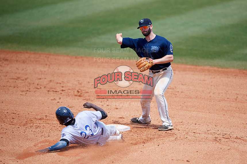 Mobile BayBears second baseman Andrew Daniel (13) throws to first base to try to complete a double play as Gabriel Guerrero (23) slides into second base during a game against the Pensacola Blue Wahoos on April 26, 2017 at Hank Aaron Stadium in Mobile, Alabama.  Pensacola defeated Mobile 5-3.  (Mike Janes/Four Seam Images)
