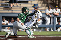 Michigan Wolverines third baseman Christian Molfetta (14) slides home a Michigan State catcher Adam Proctor (28) waits for the throw on March 22, 2021 in NCAA baseball action at Ray Fisher Stadium in Ann Arbor, Michigan. Michigan State beat the Wolverines 3-0. (Andrew Woolley/Four Seam Images)
