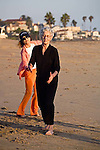 Senior woman with gray hair dressed in black workout suit exercises in dance movements with eyes closed and other woman follows on the Playa Del Rey beach in Los Angeles, California