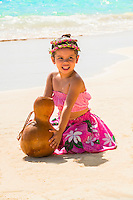 A young local girl wearing a rose lei holds an ipu (a percussive gourd used as a hula implement) on Lanikai Beach in Kailua, Windward O'ahu.