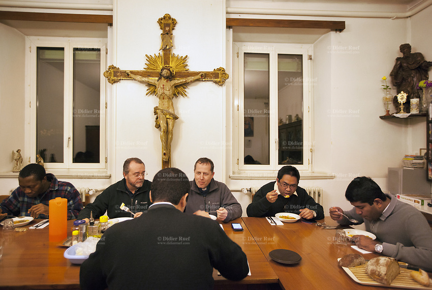 Switzerland. Canton Ticino. Lugano. «Santa Maria di Loreto » is a former convent converted to house catholic priests. On the wall, a wooden golden crucifix one meter in height with Jesus Christ on the cross. In the evening, the  priests meet for supper time in the dining room. Left to right: Don Jean Atani from Togo, Don Giorgio Paximadi from Switzerland, Don Luigi Pessina from Switzerland, Don Herve Solofoarimanana from Madagascar, Don Riju Anthoni from India. 14.03.2018 © 2018 Didier Ruef