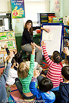 Education Elementary school Grade 1 mathematics female teacher explaning concept to class using dry erase board students with hands raised vertical