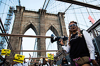NEW YORK, USA - May 25: A woman in support of Black Lives Matteren holds a speaker on the Brooklyn Bridge on the first anniversary of her death on May 25, 2021 in New York City. George Floyd's assassination in Minneapolis sparked a worldwide outcry and continued to propel the Black Lives Matter movement through different cities in the United States and the world. (Photo by Pablo Monsalve / VIEWpress via Getty Images)