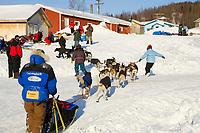 Volunteer handlers escort Bjornar Andersens team to dog park @ Ruby Chkpt 2006 Iditarod Race Alaska Winter