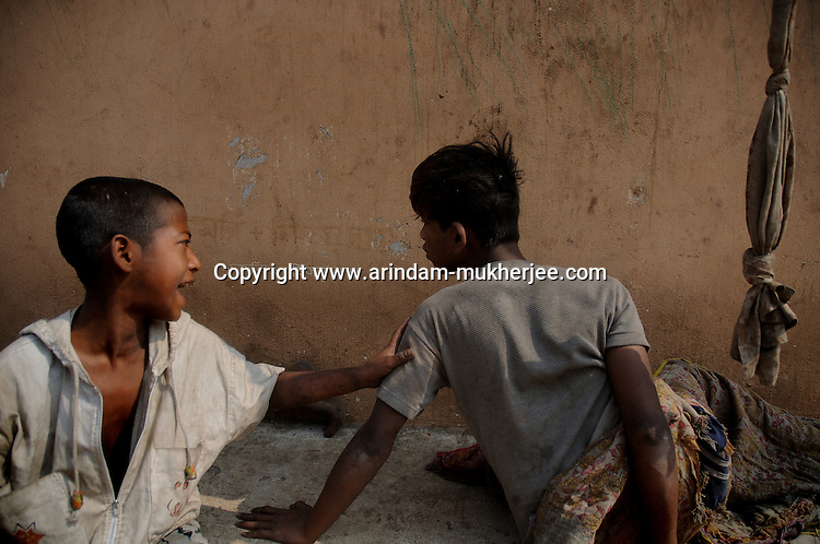 Alamgir and his friend at one of their hideouts  in the Sealdah railway premises. He is staying here for last 6 years from the time he ran away from his home due to domestic violence and poverty. As per his version his father was a drunkard and used to beat his mother for no reason. His father even could not earn enough money to buy food for their big family. Due to this traumatic situation he ran away from house at the age of seven. Ever since, the Sealdah railway station in Kolkata has been his home. As far as company is concerned, he had not much reason to miss his family. There are around 500 children, from 5 to 16 years, who live in the premises of Kolkata's second largest train terminus. Most of them addicted to Brown Sugar and sniffing industrial adhesive Dendrite. They say they don't feel hungry if they take the drugs. Their presence is conspicuous, even in a place that registers an average footfall of 1.4 million on weekdays. Their activities cover a wide range, from begging, to pulling handcarts, to petty theft, to selling odds and ends on the platform or on trains. The money, earned or ill-gotten as the case may be, is spent in procuring heroin, brown sugar, cocaine, and tubes of Dendrite. Calcutta, West Bengal, India. Arindam Mukherjee
