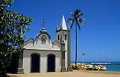 Praia do Forte, Costa do Sauipe resort, Bahia State, Brazil; small chapel with sunshades on the beach behind.