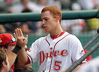 Infielder Sean Coyle (5) of the Greenville Drive is congratulated in the dugout after scoring a run in the third inning of a game against the Rome Braves on July 18, 2011, at Fluor Field at the West End in Greenville, South Carolina. (Tom Priddy/Four Seam Images)