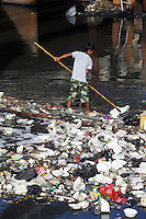 A trash collector moves along a heavily polluted waterway in central Jakarta.<br /> <br /> To license this image, please contact the National Geographic Creative Collection:<br /> <br /> Image ID: 1588076 <br />  <br /> Email: natgeocreative@ngs.org<br /> <br /> Telephone: 202 857 7537 / Toll Free 800 434 2244<br /> <br /> National Geographic Creative<br /> 1145 17th St NW, Washington DC 20036