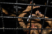 """A member of the Mara Salvatrucha gang (MS-13) shows a hand sign, representing his gang, in a cell at the detention center in San Salvador, El Salvador, 20 February 2014. Although the country's two major gangs reached a truce in 2012, the police holding cells currently house more than 3000 inmates, five times more than the official built capacity. Partly because the ordinary Mara gang members did not break with their criminal activities (extortion, street-level distribution of drugs, etc.), partly because Salvadorean police still applies controversial anti-gang law which allows to detain almost anyone for """"suspicion of gang membership"""". Accused young men are held in police detention centers where up to 25 inmates may share a cell of five-by-five metres. Here, in the dark overcrowded cages, under harsh and life-threatening conditions, suspected gang members wait long months, sometimes years, for trial or for to be transported to a regular prison."""
