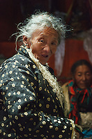 An elderly Tibentan woman in traditional clothing