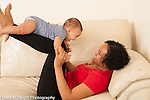 6 month old baby girl with mother playing game balanced on mother's lower legs laughing and smiling