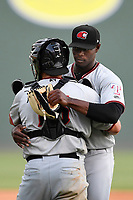 Pitcher C.D. Pelham (14) of the Hickory Crawdads hugs catcher Ricky Vanencia (15) after earning the save a game against the Greenville Drive on Sunday, July 16, 2017, at Fluor Field at the West End in Greenville, South Carolina. Hickory won, 3-1. (Tom Priddy/Four Seam Images)