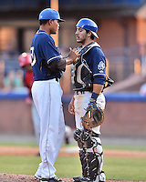 Asheville Tourists pitcher Cristian Quintin (30) and catcher Christopher Rabago (22) go over signals during a game against the Hagerstown Suns at McCormick Field on April 28, 2016 in Asheville, North Carolina. The Tourists were leading the Suns 6-5 when the game was delayed in the top of the 6th inning due to darkness. (Tony Farlow/Four Seam Images)