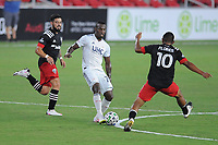WASHINGTON, DC - AUGUST 25: Cristian Penilla #70 of New England Revolution battles for the ball with Edison Flores #10 and Junior Moreno #5 of D.C. United during a game between New England Revolution and D.C. United at Audi Field on August 25, 2020 in Washington, DC.