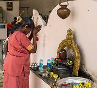 Woman Praying in front of Shiva Lingam before Entering Hindu Sri Maha Muneswarar Temple, Kuala Lumpur, Malaysia.