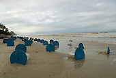 Ilheus, Bahia State, Brazil. Concrete bar tables painted blue tipped over in the sand like wheels.